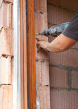 Πλαστική εγκατάσταση παραθύρων Ο εργαζόμενος τρυπά μια τρύπα για τη βίδα με τρυπάνι Στοκ εικόνες με δικαίωμα ελεύθερης χρήσης