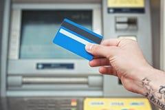Πλαστική κάρτα εκμετάλλευσης χεριών κοντά στο ATM Πληρωμή τραπεζικών καρτών Στοκ Φωτογραφία
