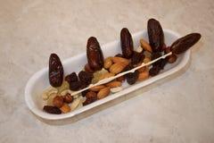 Πλαστικός δίσκος με το οβελίδιο γλασαρισμένων φρούτων σταφίδων καρυδιών ημερομηνιών στοκ εικόνες