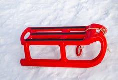 Πλαστικό κόκκινο έλκηθρο με το μαύρο ναυπηγείο πλαισίων το χειμώνα Στοκ εικόνες με δικαίωμα ελεύθερης χρήσης