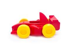 Πλαστικό κόκκινο παιχνίδι αυτοκινήτων παιχνιδιών αγώνα με τις κίτρινες ρόδες Στοκ Εικόνες