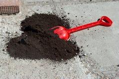 Πλαστικό κόκκινο φτυάρι με το μαύρο έδαφος Στοκ Εικόνα