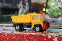 Πλαστικό φορτηγό παιχνιδιών στο χρωματισμένο πάγκο Στοκ Εικόνες