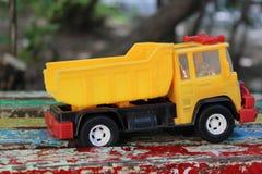 Πλαστικό φορτηγό παιχνιδιών στο χρωματισμένο πάγκο Στοκ φωτογραφία με δικαίωμα ελεύθερης χρήσης