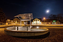 Πλατεία της πόλης με ένα φρεάτιο στη νύχτα Στοκ εικόνα με δικαίωμα ελεύθερης χρήσης