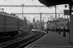 Πλατφόρμα σιδηροδρόμων με τα lampposts, τραίνα, μονοχρωματικά Στοκ Φωτογραφία