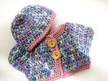 Πλεγμένα πουλόβερ και καπέλο κουκλών Στοκ Φωτογραφίες
