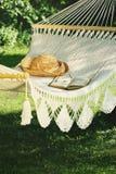 Πλεγμένη αιώρα με το καπέλο και το βιβλίο στοκ φωτογραφία