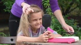 Πλεγμένο το μητέρα ponytail κορίτσι μου, το κορίτσι εξετάζει αυτή τη στιγμή την αντανάκλασή του στον καθρέφτη στη χτένα απόθεμα βίντεο