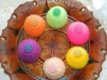 Πλεκτά καπέλα για τα αυγά Πάσχας σε ένα ξύλινο πιάτο Στοκ Φωτογραφίες