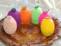 Πλεκτά καπέλα για τα αυγά Πάσχας σε ένα ξύλινο πιάτο Στοκ φωτογραφία με δικαίωμα ελεύθερης χρήσης