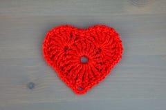 Πλεκτή καρδιά στο γκρίζο ξύλινο υπόβαθρο στοκ εικόνες