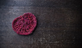 Πλεκτή κόκκινη καρδιά σε ένα ξύλινο υπόβαθρο Στοκ Φωτογραφίες