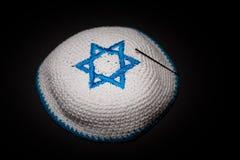 Πλεκτός kippah με το μπλε αστέρι του Δαβίδ στο μαύρο υπόβαθρο κοντά επάνω Έννοια Seder Στοκ Φωτογραφία