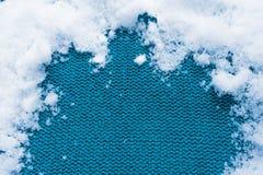 Πλεκτό υφαντικό υπόβαθρο με το χιόνι Στοκ φωτογραφία με δικαίωμα ελεύθερης χρήσης