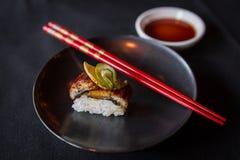 Πλευρά που πυροβολείται των σουσιών στο μαύρο πιάτο με κόκκινα Chopsticks Στοκ Εικόνες