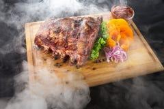 Πλευρά σχαρών με τον καπνό με τη σάλτσα και λαχανικά στον ξύλινο πίνακα Στοκ φωτογραφία με δικαίωμα ελεύθερης χρήσης