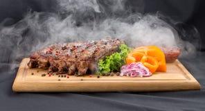 Πλευρά σχαρών με τον καπνό με τη σάλτσα και λαχανικά στον ξύλινο πίνακα Στοκ Φωτογραφίες