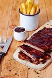 Πλευρά σχαρών χοιρινού κρέατος με τις τηγανιτές πατάτες Στοκ εικόνα με δικαίωμα ελεύθερης χρήσης
