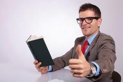 Πλευρά του νέου επιχειρησιακού ατόμου με το βιβλίο που παρουσιάζει αντίχειρα Στοκ Εικόνα