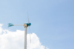 Πλευρά των ανεμόμυλων για την ηλεκτρική γεννήτρια με το μπλε ουρανό και το λευκό Στοκ Εικόνα