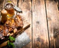 Πλευρά χοιρινού κρέατος που ψήνονται στη σχάρα με ένα τσεκούρι και μια μπύρα κρέατος Στοκ Εικόνες