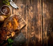 Πλευρά χοιρινού κρέατος που ψήνονται στη σχάρα με ένα τσεκούρι και μια μπύρα κρέατος Στοκ Εικόνα