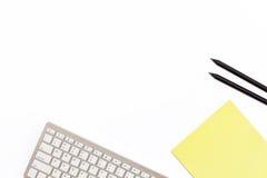 Πληκτρολόγιο υπολογιστών, κίτρινο σημειωματάριο και μαύρο μολύβι δύο σε ένα άσπρο υπόβαθρο Ελάχιστη έννοια εργασίας για το γραφεί Στοκ Εικόνα