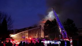 Πληρώματα πυροσβεστών που μάχονται την πυρκαγιά συγκροτημάτων κατοικιών τη νύχτα