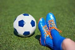 Πληρώνει το ποδόσφαιρο αγοριών στις μπότες ποδοσφαίρου με τη σφαίρα στη χλόη Στοκ εικόνα με δικαίωμα ελεύθερης χρήσης