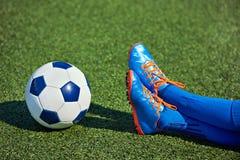 Πληρώνει το ποδόσφαιρο αγοριών στις μπότες ποδοσφαίρου με τη σφαίρα στη χλόη Στοκ φωτογραφία με δικαίωμα ελεύθερης χρήσης
