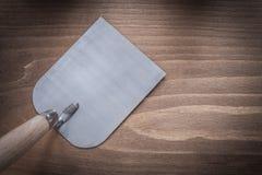 Πλινθοδομή μετάλλων trowel στην εκλεκτής ποιότητας ξύλινη κατασκευή πινάκων συμπυκνωμένη Στοκ Φωτογραφία