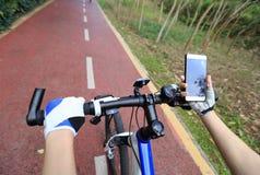 Πλοηγός ΠΣΤ χρήσης χεριών ποδηλατών στο smartphone Στοκ Φωτογραφία