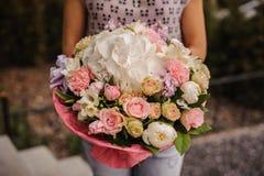 Πλούσια δέσμη των άσπρων και ρόδινων λουλουδιών στα χέρια Στοκ εικόνες με δικαίωμα ελεύθερης χρήσης