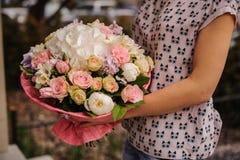 Πλούσια δέσμη των άσπρων και ρόδινων λουλουδιών στα χέρια Στοκ Φωτογραφία