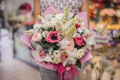 Πλούσια δέσμη των άσπρων και ρόδινων λουλουδιών στα χέρια Στοκ Φωτογραφίες