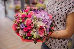 Πλούσια δέσμη των άσπρων και ρόδινων λουλουδιών στα χέρια Στοκ Εικόνες