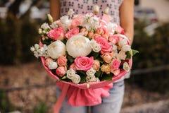 Πλούσια δέσμη των άσπρων και ρόδινων λουλουδιών στα χέρια Στοκ φωτογραφία με δικαίωμα ελεύθερης χρήσης