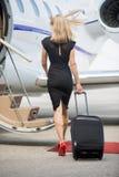 Πλούσια γυναίκα με τις αποσκευές που περπατά προς ιδιωτικό Στοκ Εικόνες