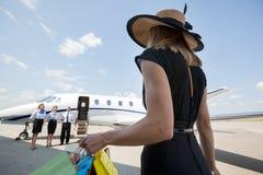 Πλούσια γυναίκα με τις τσάντες αγορών που περπατά προς Στοκ Φωτογραφία