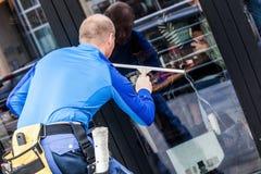 Πλυντήριο παραθύρων που λειτουργεί στην οικοδόμηση υπαίθρια Στοκ φωτογραφία με δικαίωμα ελεύθερης χρήσης