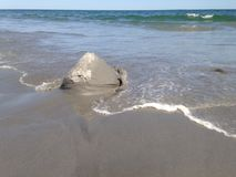 Πλύση κάστρων άμμου μακριά Στοκ Εικόνα