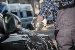Πλύσιμο αυτοκινήτων με το σφουγγάρι και τον αφρό στο δρόμο Στοκ Φωτογραφία