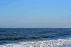 Πλύσιμο κυμάτων επάνω επάνω στην αμμώδη παραλία Στοκ Φωτογραφίες