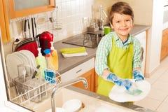 Πλύσιμο μικρών παιδιών dished στο νεροχύτη με τη σφουγγαρίστρα και το σαπούνι Στοκ Εικόνες