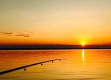 Ράβδος αλιείας ψαράδων στο ηλιοβασίλεμα Στοκ Εικόνα