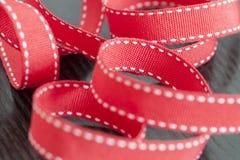 Ράβοντας βελόνα σε μια κόκκινη κορδέλλα στοκ εικόνες