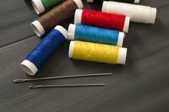 Ράβοντας βελόνα και χρωματισμένα νήματα στροφίων, πολύχρωμα νήματα στροφίων, ράψιμο και ράβοντας βελόνες, ψαλίδι και ψαλίδι, που  Στοκ εικόνες με δικαίωμα ελεύθερης χρήσης