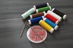 Ράβοντας βελόνα και χρωματισμένα νήματα στροφίων, πολύχρωμα νήματα στροφίων, ράψιμο και ράβοντας βελόνες, ψαλίδι και ψαλίδι, που  Στοκ φωτογραφία με δικαίωμα ελεύθερης χρήσης