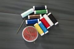 Ράβοντας βελόνα και χρωματισμένα νήματα στροφίων, πολύχρωμα νήματα στροφίων, ράψιμο και ράβοντας βελόνες, ψαλίδι και ψαλίδι, που  Στοκ φωτογραφίες με δικαίωμα ελεύθερης χρήσης